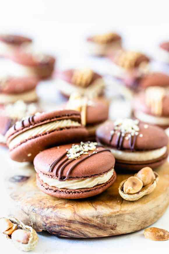Peanut Butter Macarons topped with peanut butter drizzle and chopped peanuts on a board