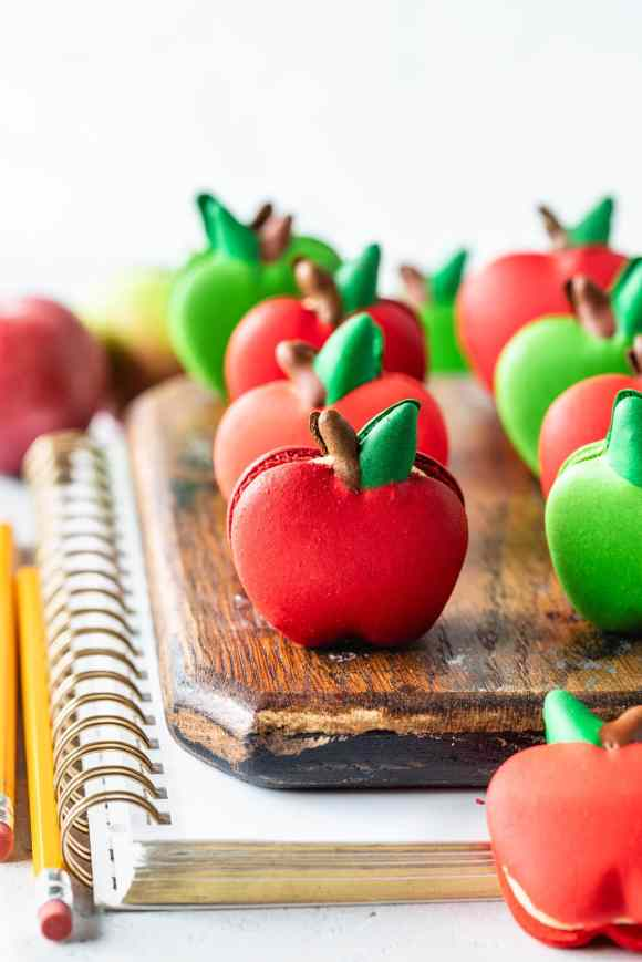macarons shaped like apples on top of a wooden board and a notebook with pencils on the side.