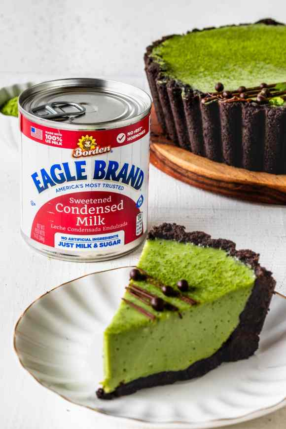 Matcha Pie with oreo crust and drizzled with chocolate and callebaut crispearls sliced with a can of Eagle Brand® condensed milk in the back