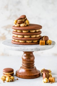 Caramel Macaron Cake layers of chocolate macaron shells filled with caramel buttercream topped with mini macarons, caramel popcorn.
