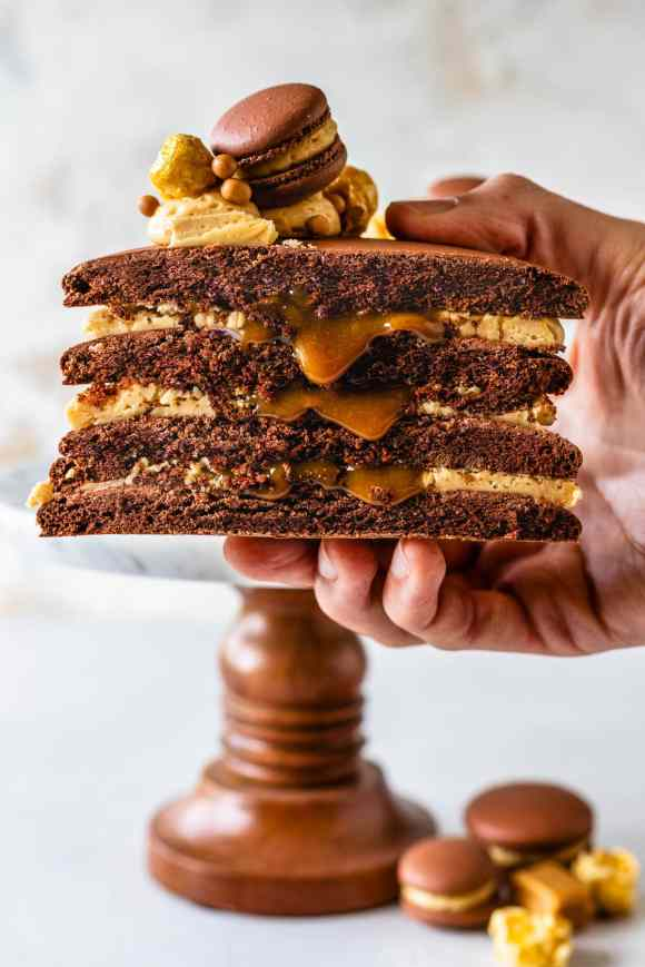 hand holding a macaron cake sliced in half filled with caramel.