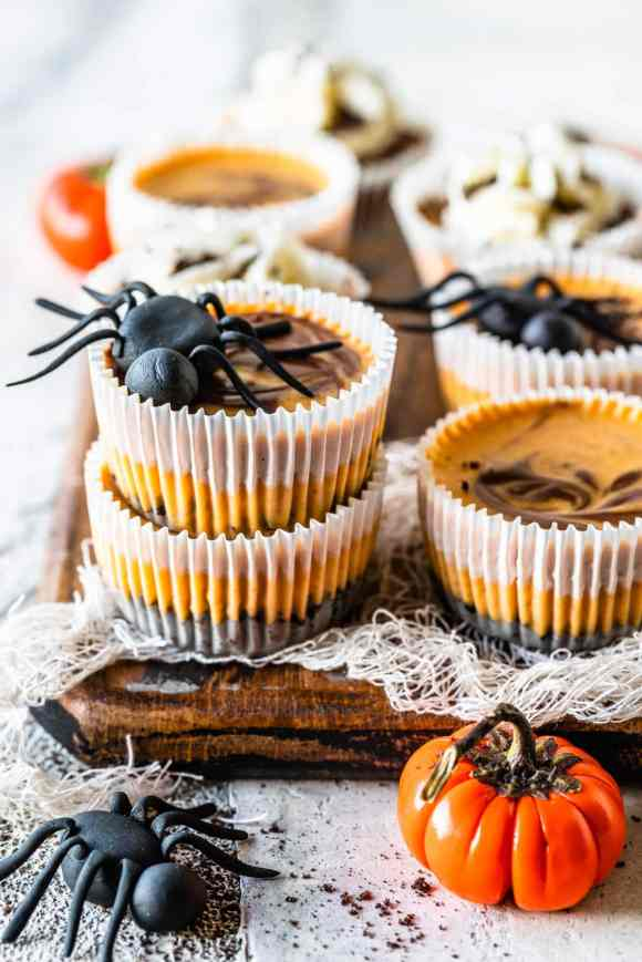 Chocolate Pumpkin Mini Cheesecakes stacked, with a fondant spider on top. Around there are pumpkins and more mini cheesecakes decorating. they are topped with oreo crumbs and the cheesecakes on the back are topped with whipped cream.