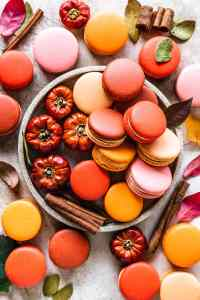 Pumpkin caramel macarons in a plate with little pumpkins on the side, the macarons have various colors, from orange tones, pink, crimson, and orange, also some cinnamon sticks around the picture and leaves.