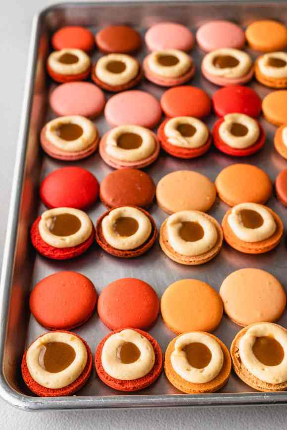 macaron shells filled with a dome of buttercream frosting, and caramel sauce in the middle.