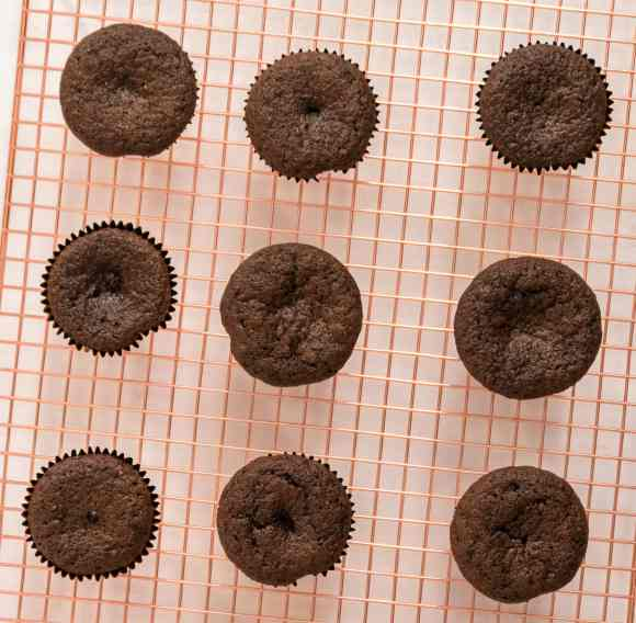 chocolate cupcakes on a cooling rack, seen from the top.