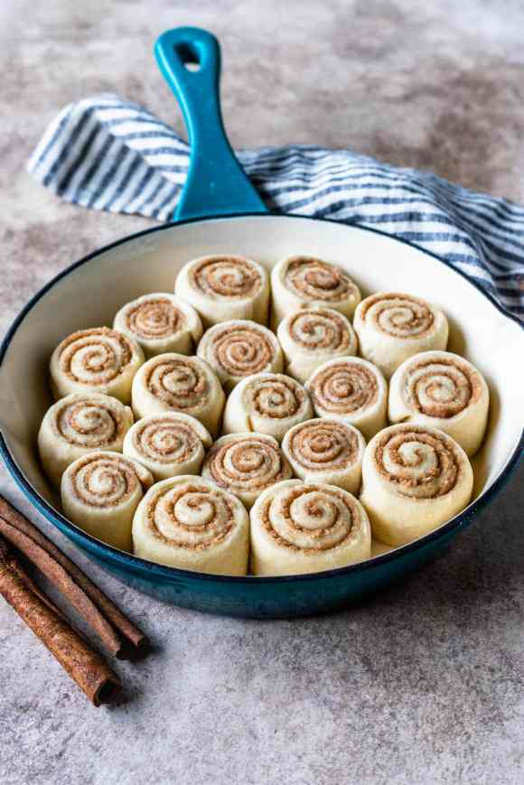 Mini Cinnamon Rolls before baking, placed in a blue skillet.