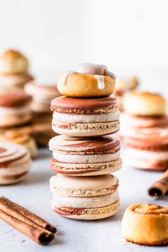 stacked cinnamon macarons topped with a cinnamon roll.