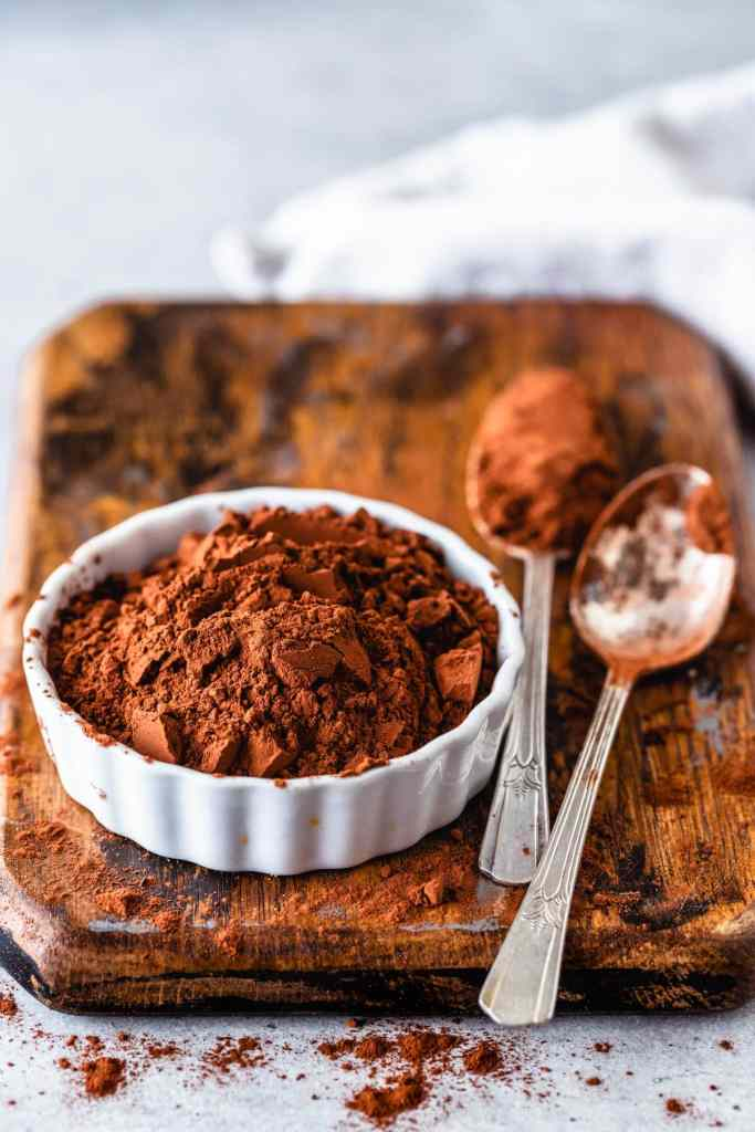 cocoa powder in a small ramekin with two spoons on the side.
