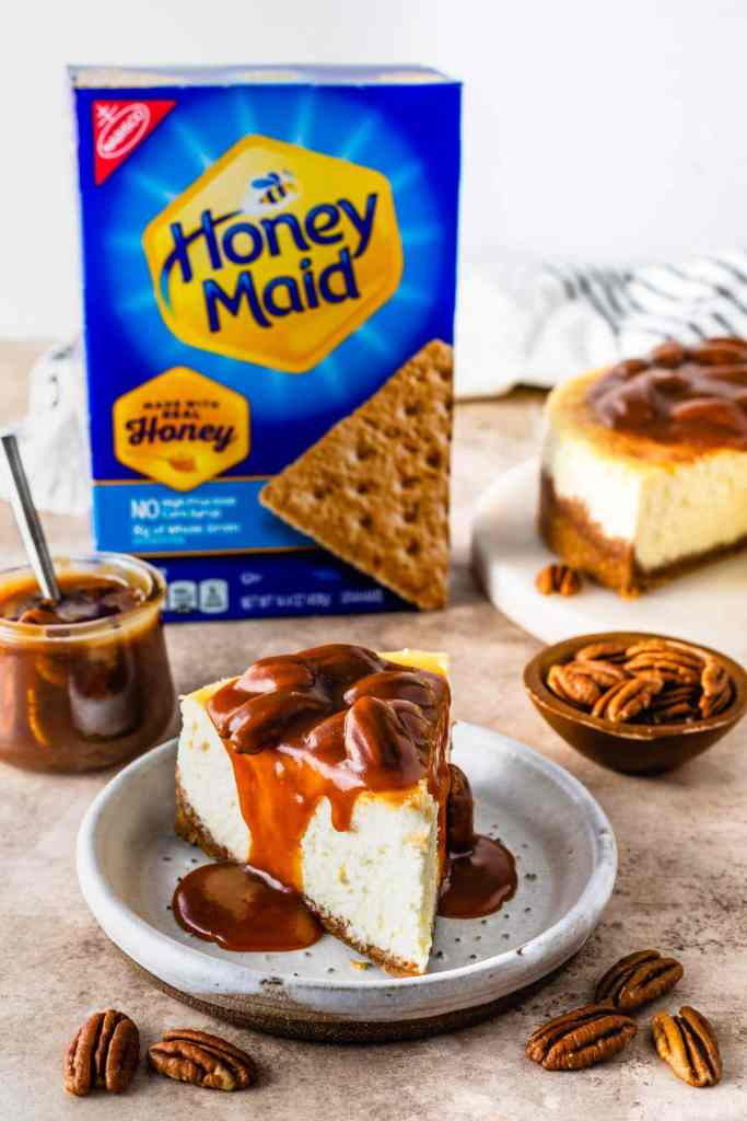 Pecan Pie Cheesecake topped with caramel sauce, with a box of honey maid graham crackers in the back.