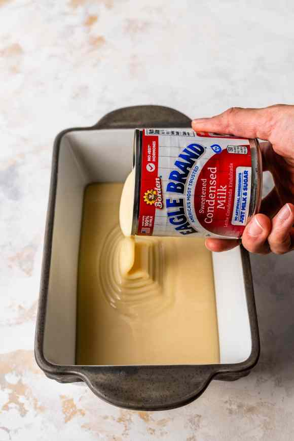 pouring condensed milk in a pan to make oven dulce de leche.