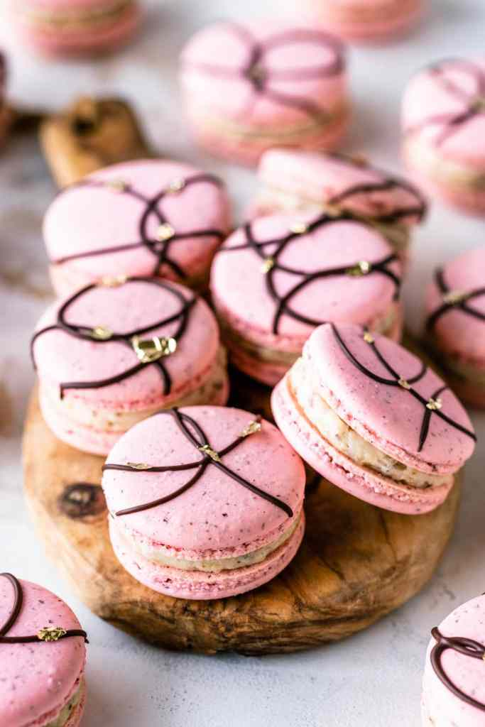 pink macarons with a chocolate decoration on top and golden leaf accents.