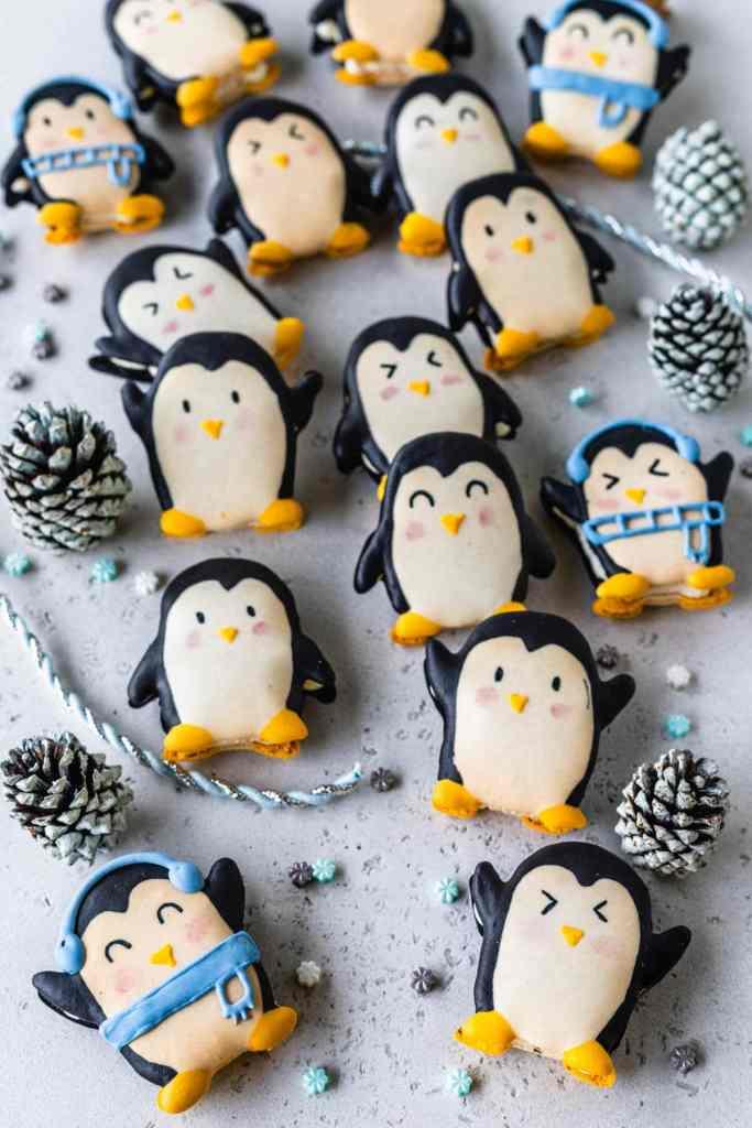 macarons shaped like penguins inside of a cookie box.