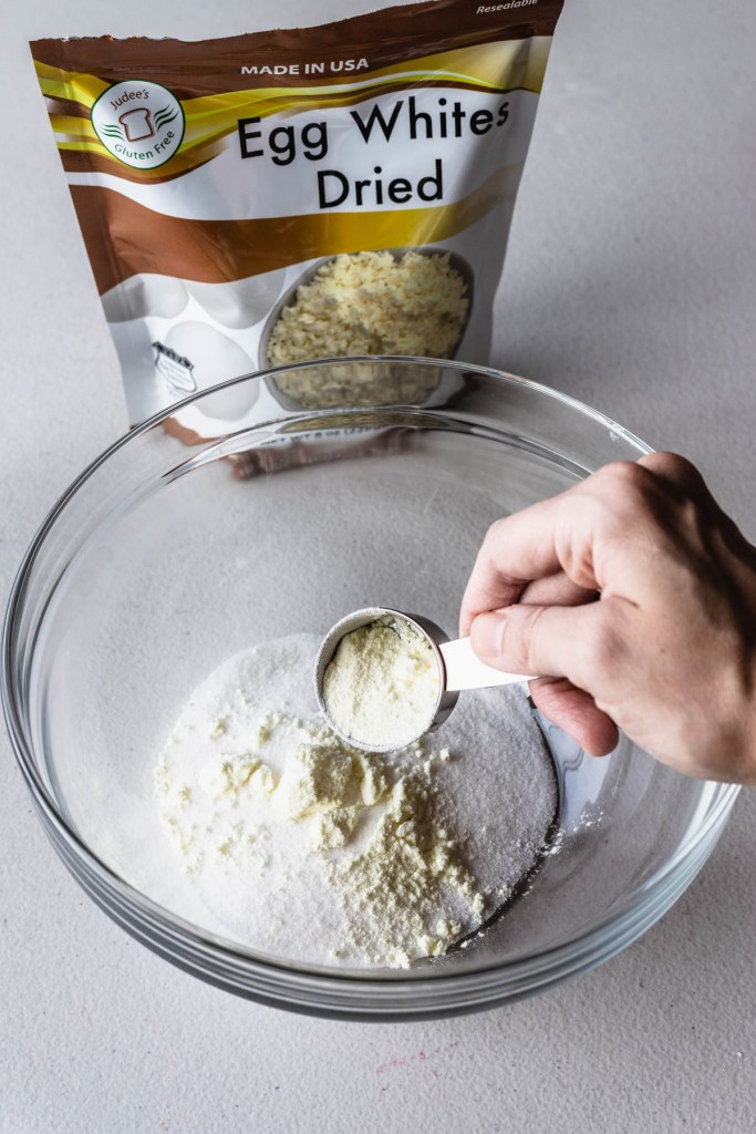 pouring egg white powder over granulated sugar in a bowl.