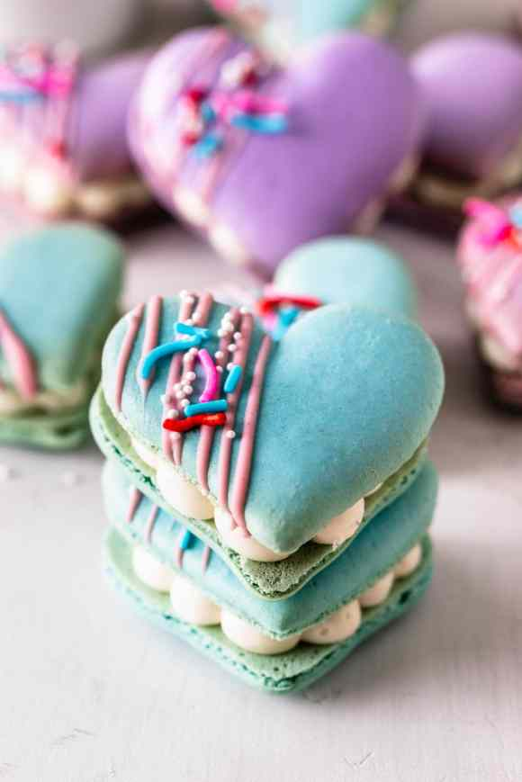 stacked heart macarons filled with brownies and cream cheese frosting, topped with a drizzle of melted chocolate and sprinkles.