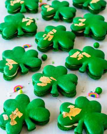 Shamrock macarons with gold edible leaf on top, surrounded by sprinkles.