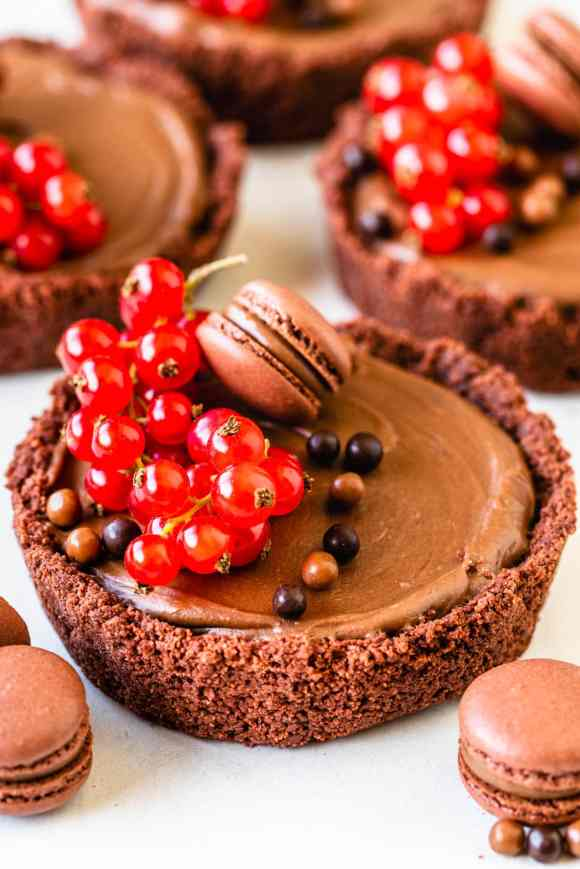 Mini pies filled with chocolate cheesecake filling topped with mini macarons, red currants.
