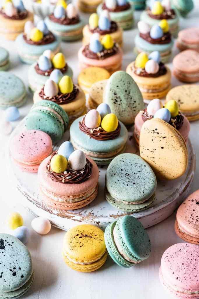 easter macarons topped with a nest made out of chocolate frosting, and cadbury eggs.