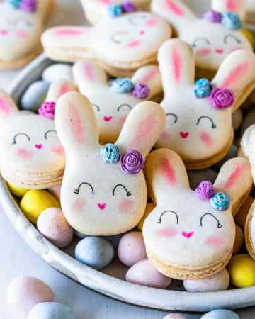 Bunny Macarons with a little chocolate rose in the ear, on a plate with cadbury eggs.