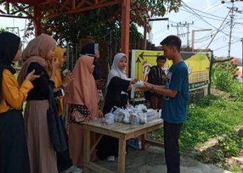 Mahasiswa IAIN Parepare sedang memberikan nasi bungkus kepada warga. --foto hamdan/pijarnews--