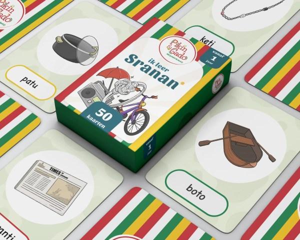 Doos speelkaarten met daarom heen losse kaarten met verschillende afbeeldingen voorwerpen