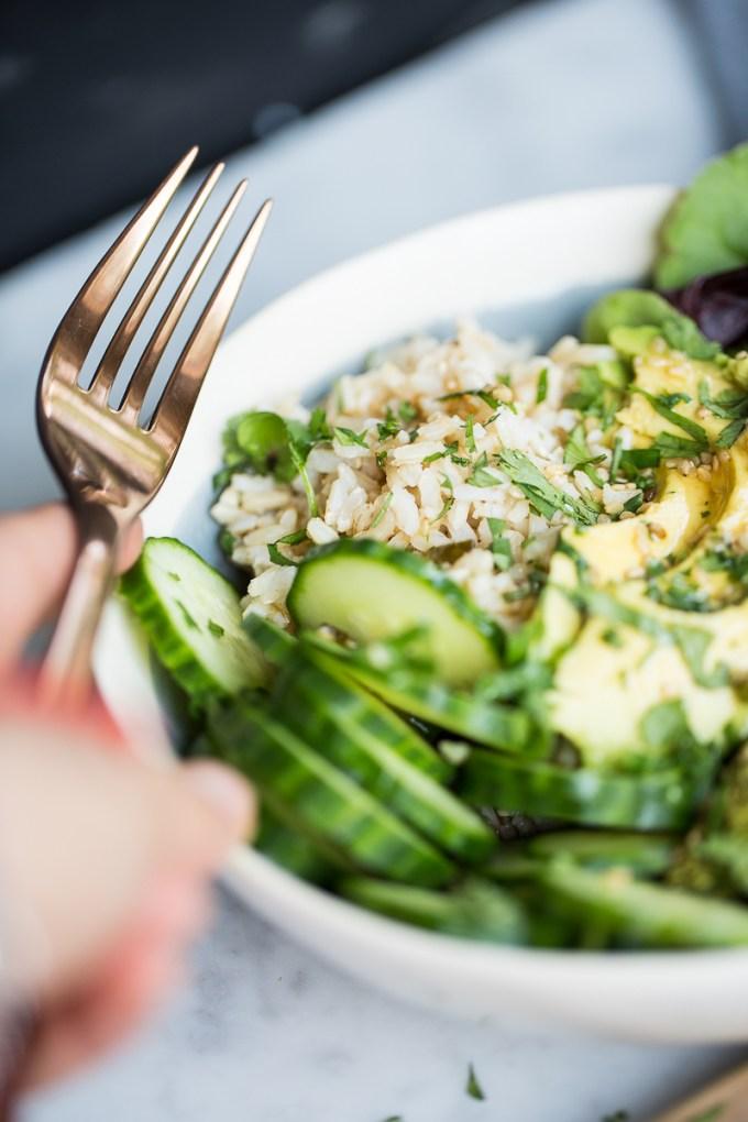 Plato de arroz integral con verduras verdes y aderezo oriental