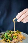 Receta de verduras de invierno rostizadas con aderezo de pimiento rojo y granos ancestrales.