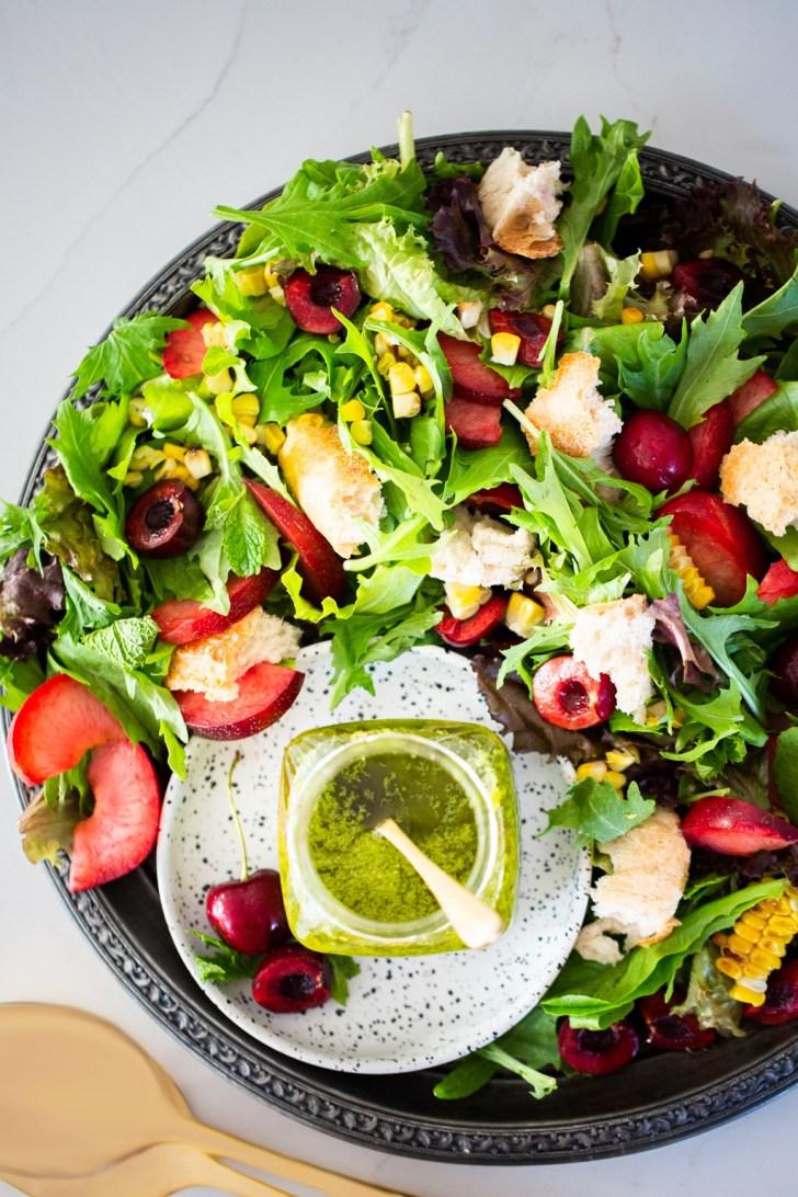 Ensalada de verano con cerezas, pan, fruta y aderezo de albahaca y aguacate.