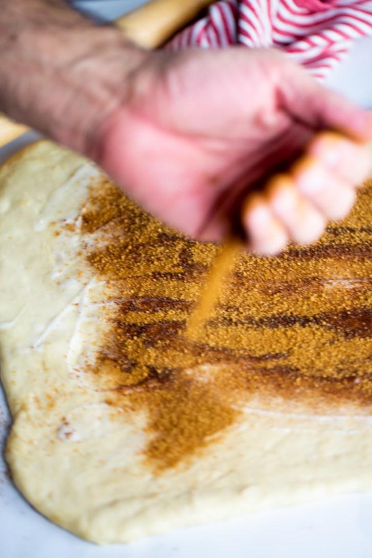 Sprinkling cinnamon to dough