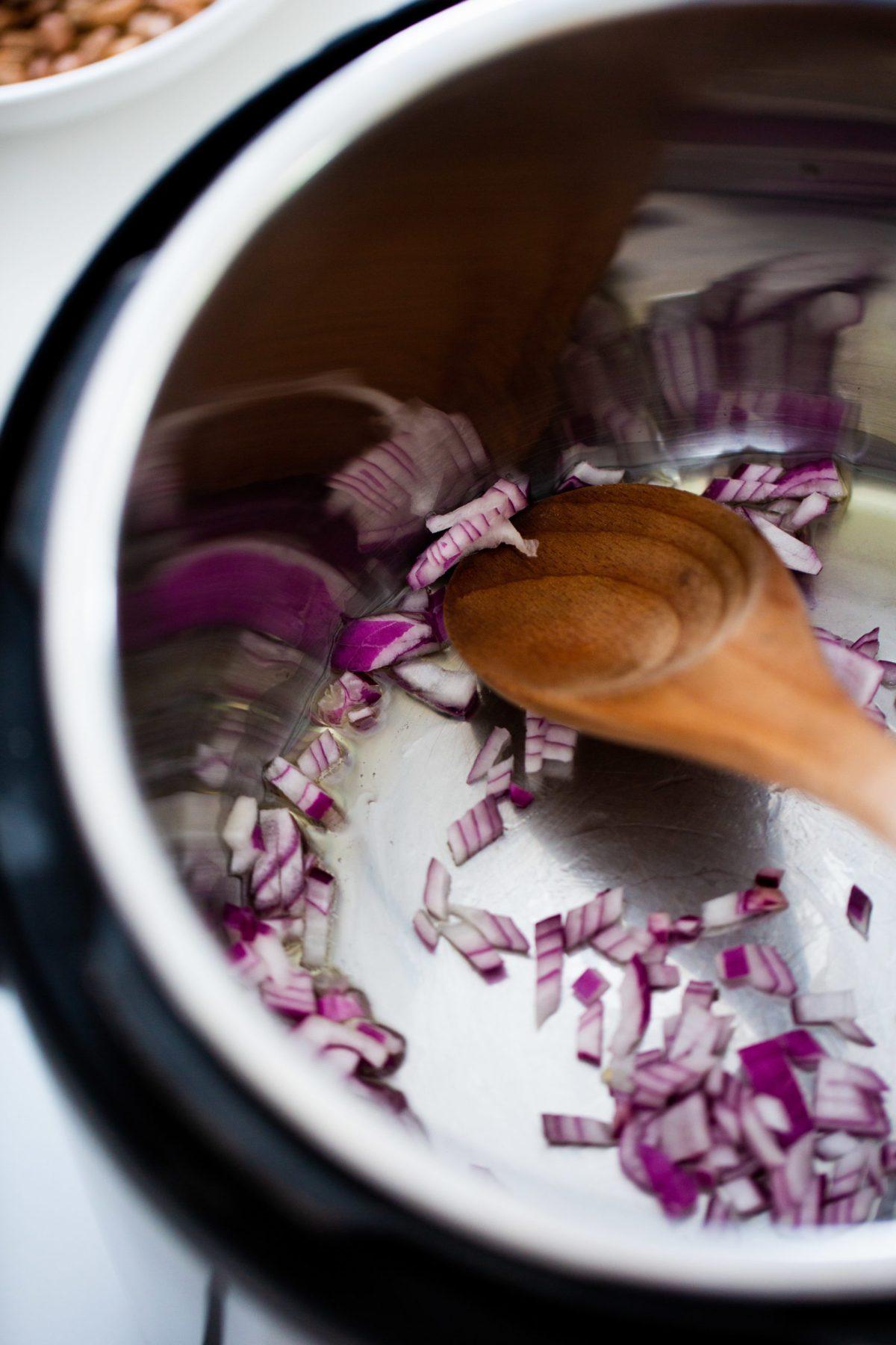 salteando cebolla en la instast pot para hacer frijoles refritos