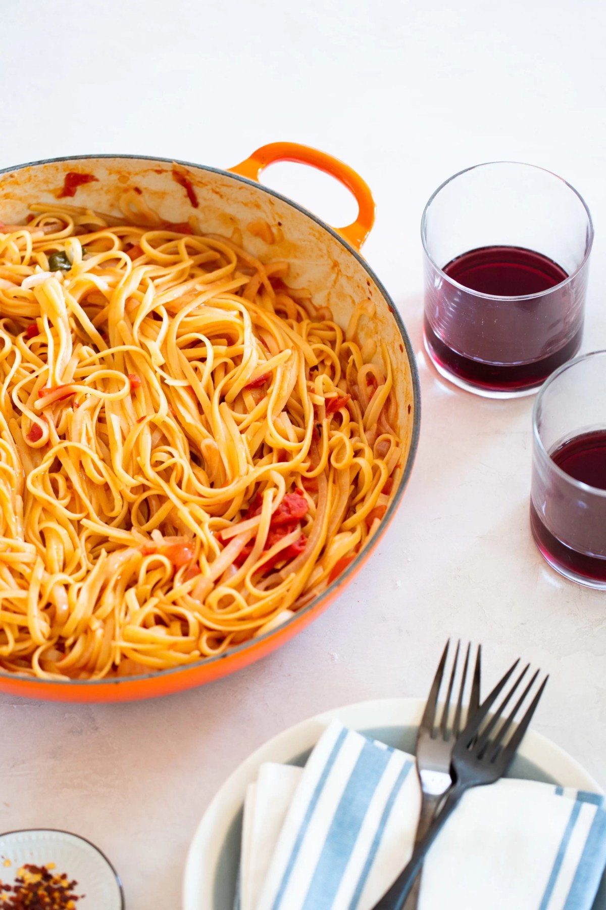 PAsta con tomate en un sarten con vasos de vino tinto