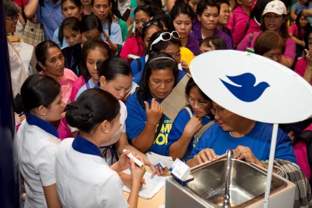 Women line up to receive Dove samples at the Dove booth inside the NBC Tent.