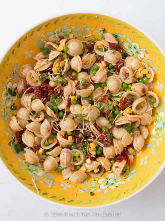 Full of fresh basil and veggies, this lightly dressed sun-dried tomato pasta salad is a refreshing and flavorful side dish for sandwiches, a potluck, or a light lunch! Copycat recipe from Beyond Bread in Tucson, AZ. | www.pinchmeimeating.com