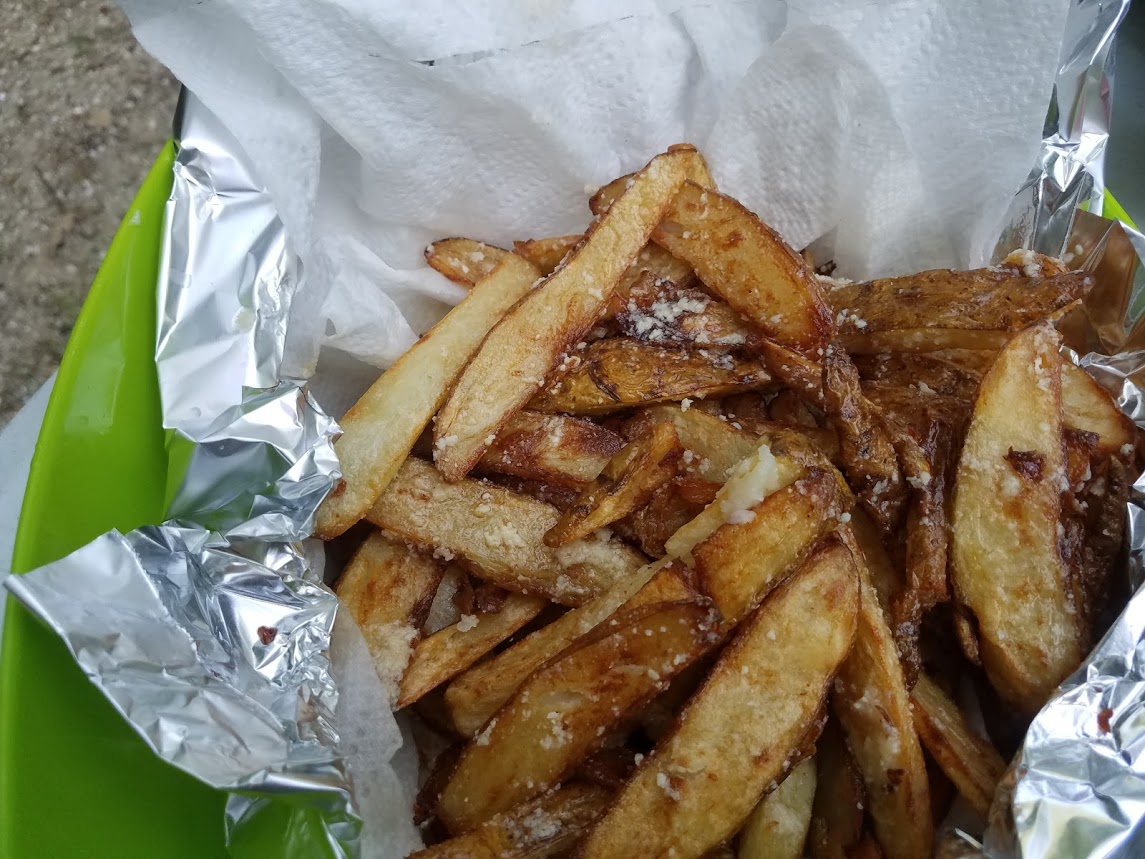 Buttery garlic fries in a basket lined with foil and paper towels