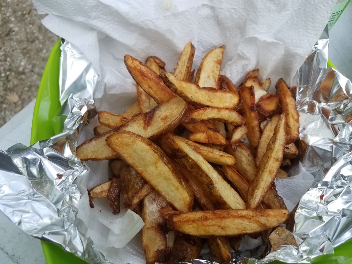Cooked, unseasoned, french fries in a bowl lined with foil and paper towels