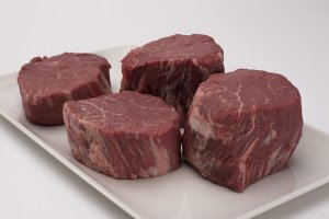 four raw filet mignon steaks on a white square plate
