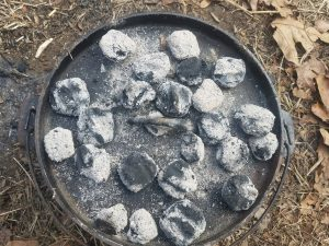 a dutch oven covered with several charcoal briquettes