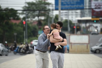 """TOPSHOT - American Gordon Lake (L) and his Spanish husband Manuel Valero (R) play with their daughter Carmen after a hearing at The Central Juvenile and Family Court in Bangkok on March 30, 2016. A foreign same-sex couple battling a local Thai surrogate for custody over their infant daughter said on March 30 their lives had been """"destroyed"""" by the 14-month legal war that has prevented their family from returning home. Manuel Valero, from Spain, and his American husband Gordon Lake were blocked from leaving Thailand with their daughter Carmen after the surrogate refused to sign necessary paperwork following the birth last January. / AFP / LILLIAN SUWANRUMPHA (Photo credit should read LILLIAN SUWANRUMPHA/AFP/Getty Images)"""