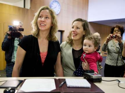 Corine (L) and Audrey Schep sign, along with their child Dieuwke, the first certificate of approvalthe first certificate of approval for a co-mother at the Zwolle city hall, The Netherlands, on April 1, 2014. Lesbian couples are now able to be both legal parents of a child of one of them, without going through complicated and costly procedures. AFP PHOTO / ANP - JERRY LAMPEN = netherlands out        (Photo credit should read JERRY LAMPEN/AFP/Getty Images)