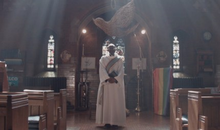 Openly gay priest Reverend Jide Macaulay appears dressed in the canonical robes in a clip of Stonewall's BAME Voices documentary.
