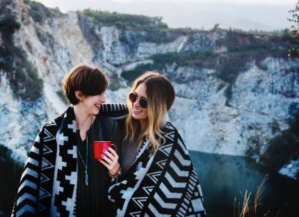 Same-sex partners enjoy a warm beverage after climbing cliffs in one of the best countries for gay couples on honeymoon.