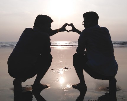 Same-sex partners share an affectionate moment on a beach that could be located in one of the best countries for gay couples on honeymoon.