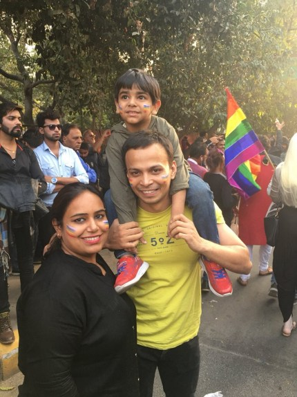 Man, woman and child pose for a photo at the first Indian Pride parade since the decriminalisation of gay sex