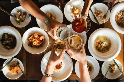People clink drinks over a meal
