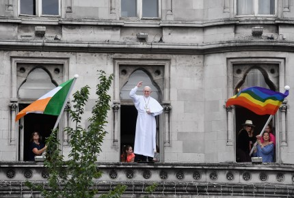 The Irish flag and a rainbow flag are placed on each side of a model of Pope Francis during his visit to Ireland.