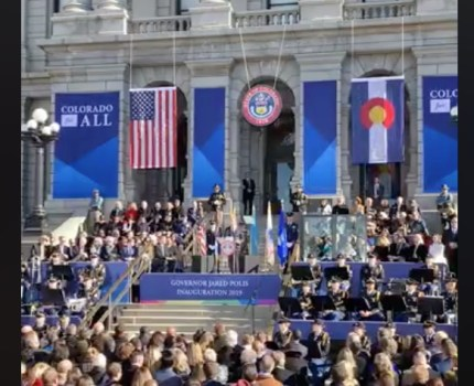 The stage at the Jared Polis inauguration was dressed with a rainbow