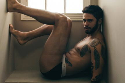 A man leans against a wall in his underwear