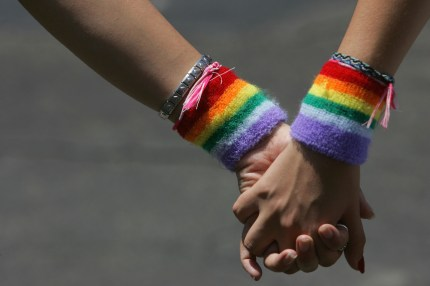 Girls holding hands with rainbow LGBT wristbands.