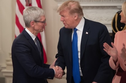"""US President Donald Trump shakes hands with Apple CEO Tim Cook after calling him """"Tim Apple"""" during the first meeting of the American Workforce Policy Advisory Board in the State Dining Room of the White House in Washington, DC, March 6, 2019."""