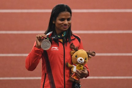 Silver medallist India's Dutee Chand celebrates during the victory ceremony for the women's 200m athletics event during the 2018 Asian Games in Jakarta. (ANTHONY WALLACE/AFP/Getty Images)