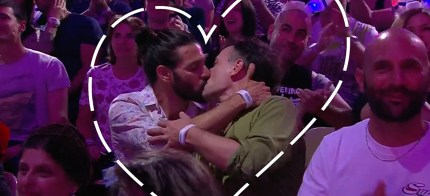 Same-sex couple kisses for the camera during Dana International's performance at Eurovision.